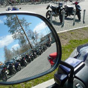 Mopoja ja skoottereita lukion pihalla. Rovaniemen Lyseonpuiston lukion pihalla seisoo pitkä moporivistö.