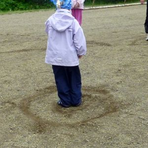 Pieni tyttö seisoo hiekkakentällä ringin keskellä tervapata-leikissä.