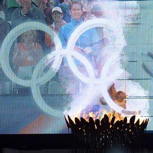 Olympiatuli palamassa kenttätapahtumia esittävän jättinäytön edustalla Lontoon olympiastadionilla.