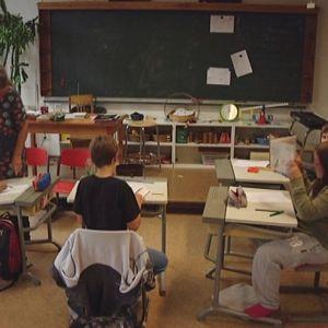 Neljä oppilasta ja opettaja luokkahuoneessa.
