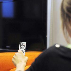 Nainen kaukosäädin kädessä television edessä.