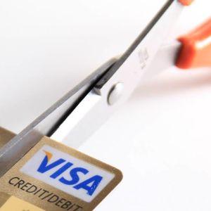 Kuvassa sakset leikkaavat luottokortin kulmaa.