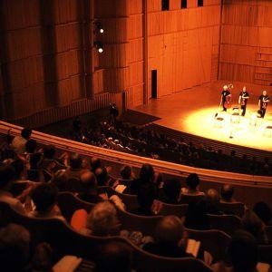 Kamarimusiikkitaiteilijoita ja yleisöä Kuhmo-talon konserttisalissa.
