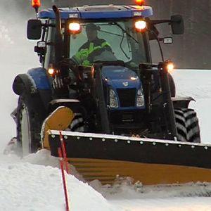 Traktori auraa lumista tietä