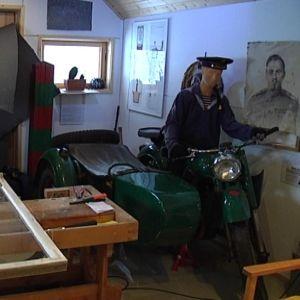 Kyläavustaja kunnostaa ikkunanpokia Igor-museon takahuoneessa.