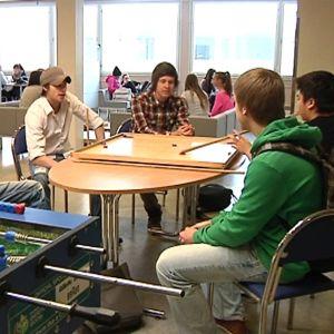 kuvassa ruotsinkielsien lukion aulatiloja, opiskelijoita pöydän ympärillä.