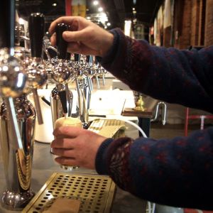 Juomanlaskija laskee olutta lasiin.