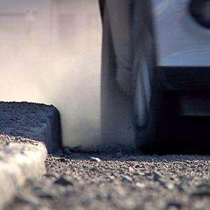 Katupöly nousee sankkana pilvenä kadun pinnasta henkilöauton ajaessa ohi. Mies kävelee jalkakäytävää pitkin muovikassi kädessä.