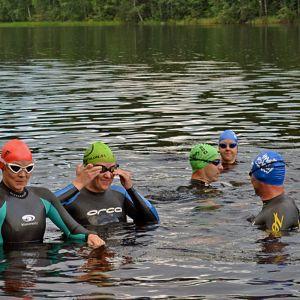 Triathlonistit harjoittelevat vedessä.