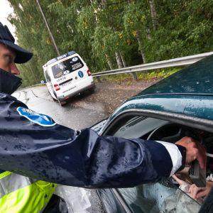 Poliisi puhalluttaa autoilijaa.