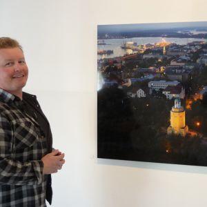 Jari Varpenius seisoo maisemakuvan edessä