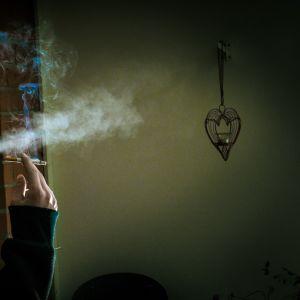 mies polttaa parvekkeella tupakkaa.