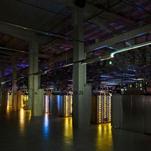 Iso halli on täynnä värikkäissä valoissa välkkyviä serveriräkkejä.
