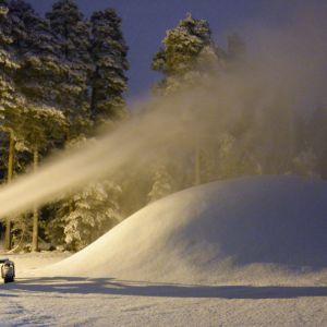 Kuvassa lunta syöksevä lumitykki ja lumikasa