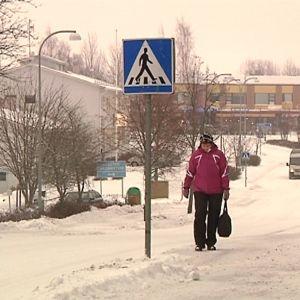 Nainen kävelee lumista kylän raittia