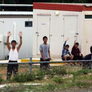 Turvapaikan hakijat vilkuttavat kuvaajalle Joulusaarella sijaitsevan pakolaiskeskuksen aidan yli.