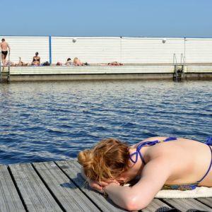 Nuori nainen ottaa aurinkoa uimarannan laiturilla