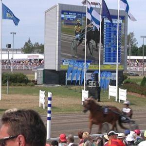 Porin raviradalla juoksee hevosia. Katsomosa paljon yleisöä