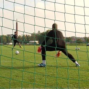 Jalkapallomaalivahti torjuu palloa.