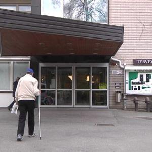 Ihminen kävelee terveysaseman edessä.