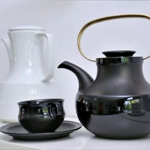 Musta teekannu kullatulla kahvalla sekä tyyliin sopiva teekuppi.