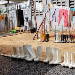Liberialainen sairaanhoitaja desinfioi kumisaappaita Monroviassa.