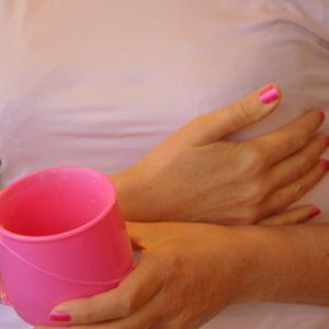 Nainen pitelee pinkkiä mukia kädessään.