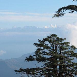 Näkymä kohti vuoristoa, jonka yläpuolella on pilviä. Autereinen sää.