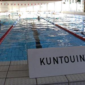 """Uimahallin allasreunuksella kyltti, jossa lukee """"kuntouinti""""."""