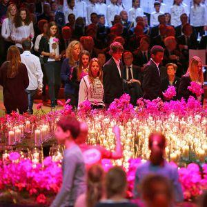 Uhrien omaiset tuovat kukkia mkynttilöiden viereen