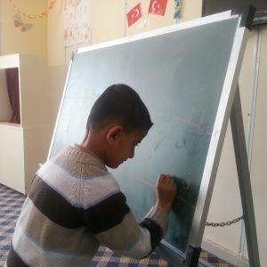 Syyrialaispoika harjoittelee kirjoittamista äidinkielen tunnilla yhdessä leirin kolmesta koulusta.