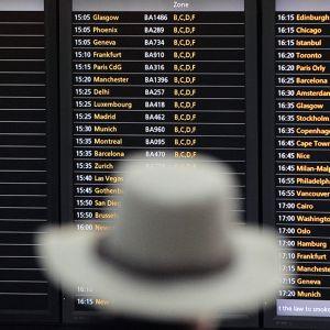 Lentomatkustaja katsoo lentojen aikatauluja lentokentällä.