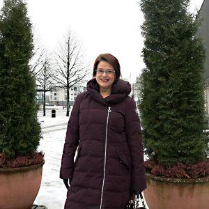 Nainen seisoo ulkona havupuiden vieressä.