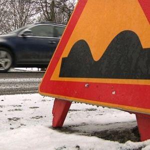 Epätasainen tie -liikennemerkki tien laidassa