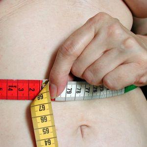 Lihava nainen pitelee mittanauhaa vatsansa ympäri.