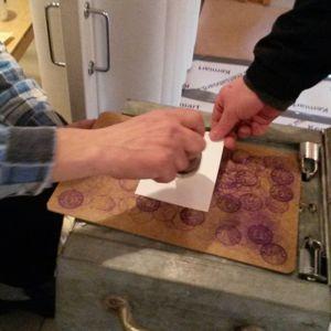 Vaalitoimitsija lyö leiman äänestyslippuun.