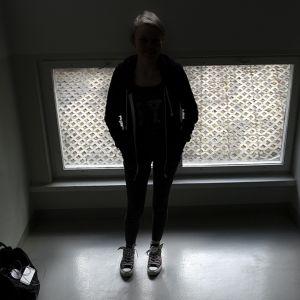 Nuori nainen seisoo ikkunan edessä.