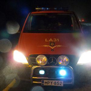 Pelastuslaitoksen auto pimeällä tiellä