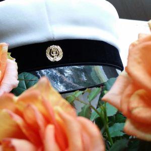 Kuvassa ylioppilaslakki ruusujen keskellä