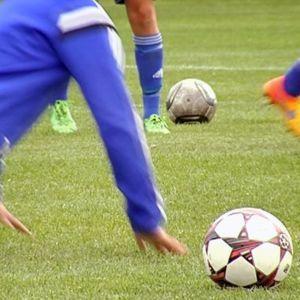 Nuoret pelaajat harjoittelevat jalkapalloa.