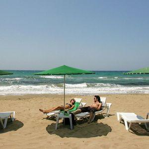 Pariskunta hiekkarannalla aurinkotuoleissa.