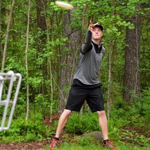 Mies heitää frisbeen kohti frisbeegolfkoria.