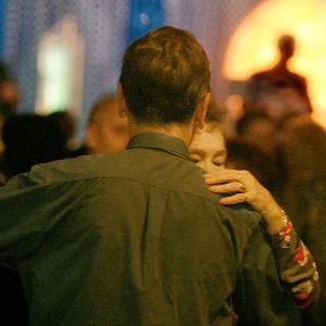 Mies ja nainen tanssivat, takana näkyy siluetissa orkesterin