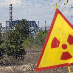 Radioaktiivisuusvaroitusmerrki ja Tsernobylin ydinvoimala-aluetta.