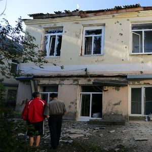 Kolme ihmistä vahingoittuneen rakennuksen luona.