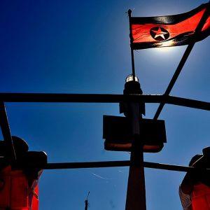 Kaksi ulkomaista turistia ottaa kuvia höyrylaivaristeilyllä Pohjois-Koreassa. Maan lippu liehuu tuulessa.
