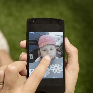 Äiti katsoo lapsensa kuvaa kännykästä.