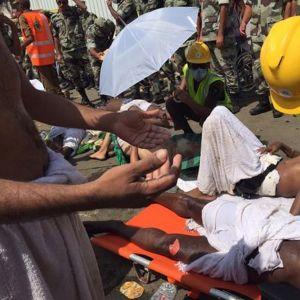 Pelastusmies hoitaa paareilla makaavaa loukkaantunutta miestä. Maassa makaa muita uhreja.