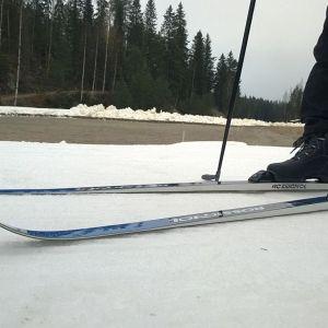 Ensilumenladulla hiihtäjällä sukset jalassa.