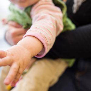 Lapsen käsi kurkottaa kohti katsojaa.